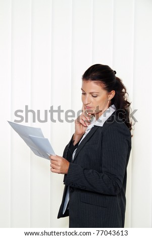 Businesswoman reading a letter in the office. Message from the attorney or tax office. - stock photo