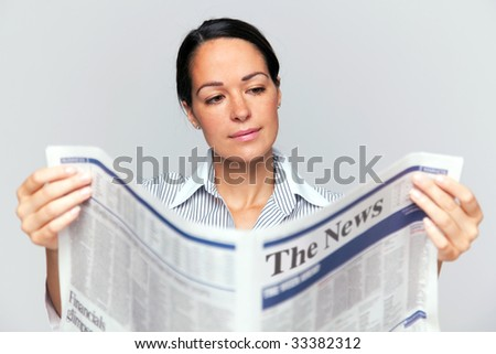 Businesswoman reading a newspaper, focus is on her face and newspaper is blurred. - stock photo