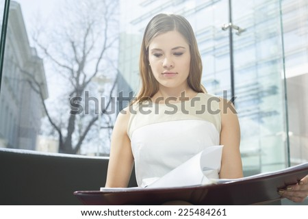 Businesswoman reading file in office - stock photo