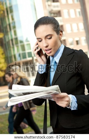 businesswoman reading newspaper and talking on phone - stock photo
