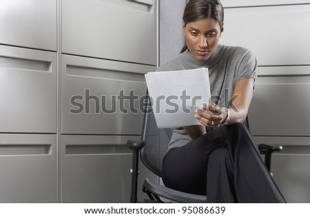 Businesswoman reading paperwork