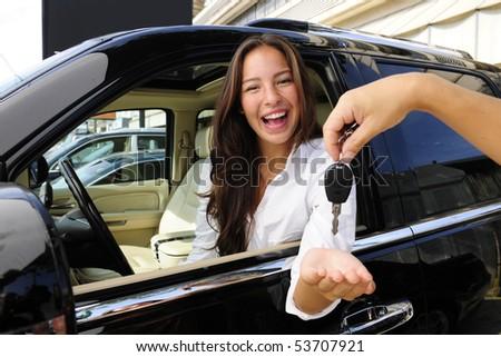 businesswoman receiving keys of her new status car from dealer - stock photo