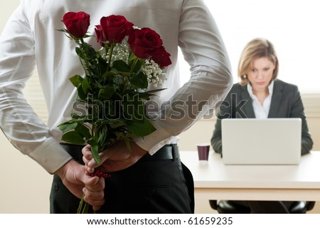 Businesswoman receiving red roses in the office - Valentine's day, Birthday or Anniversary - stock photo