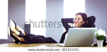 Businesswoman relaxing at her desk in her office - stock photo