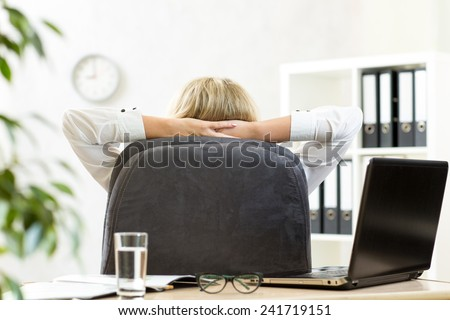 Businesswoman relaxing in office sitting back in chair with hands behind neck - stock photo