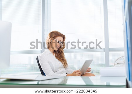 Businesswoman relaxing in office watching movies on tablet computer  - stock photo
