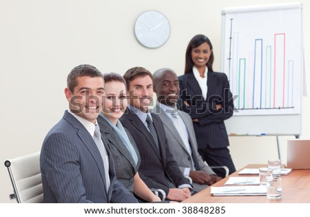 Businesswoman reporting to sales figures to her colleagues in a meeting - stock photo