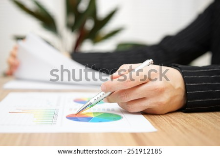 Businesswoman reviewing report and browsing document - stock photo