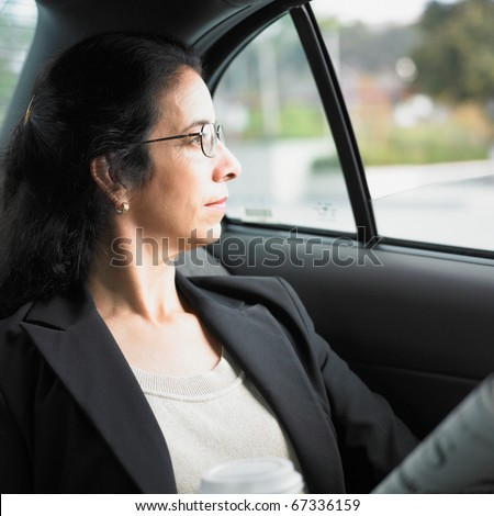 Businesswoman riding in the back of a car
