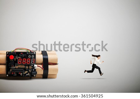 businesswoman running away from big bomb with timer over light grey background - stock photo