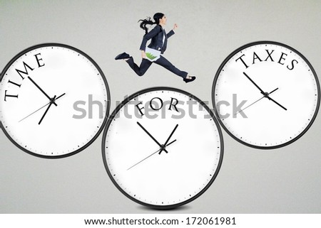 Businesswoman running over the clocks with time for taxes - stock photo