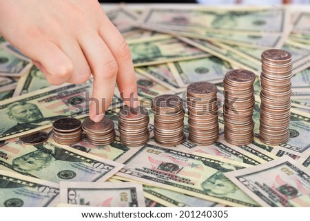 Businesswoman's fingers walking up stack of coins on dollar bills at desk - stock photo