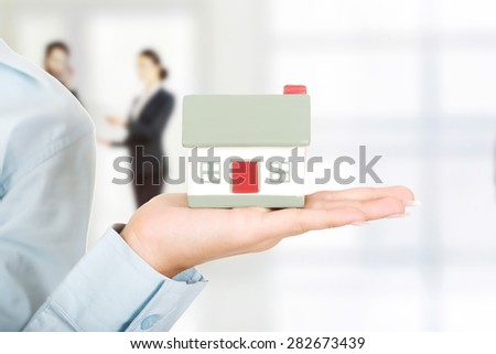 Businesswoman's hand presenting a house model. - stock photo