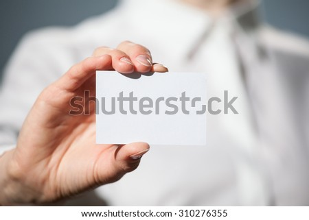 Businesswoman's hand showing business card on dark background