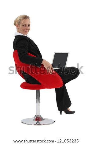Businesswoman sat in designer chair with laptop - stock photo