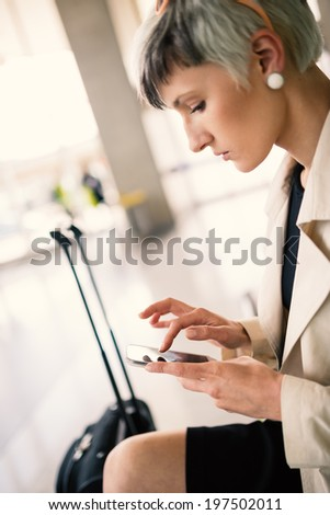 Businesswoman sending message with mobile phone at Charles de Gaulle airport, Paris.  - stock photo