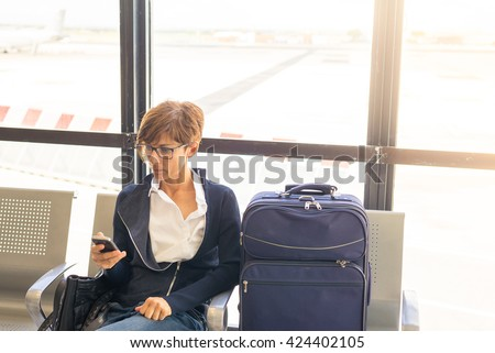 Businesswoman sending message with mobile phone sitting in airport terminal. Concept of people sharing informations with new technology while traveling. Selective focus on smart phone. - stock photo