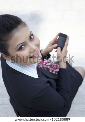 Businesswoman sending message with smartphone - stock photo