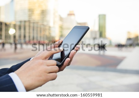 Businesswoman sending messages with her smart phone in front of building   - stock photo