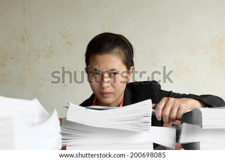 businesswoman serious with pile of paper - stock photo
