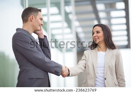 Businesswoman shaking hands with businessman in front of corporate office building