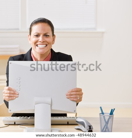 Businesswoman shaking monitor - stock photo