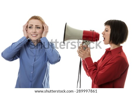Businesswoman shouting at another woman using a bullhorn - stock photo
