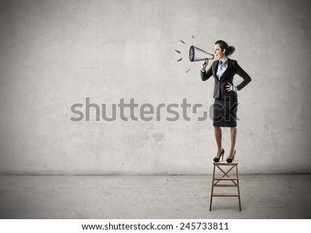 Businesswoman shouting into a megaphone  - stock photo