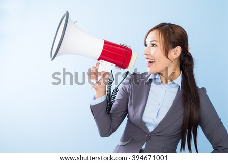Businesswoman shouting with loudspeaker over blue background
