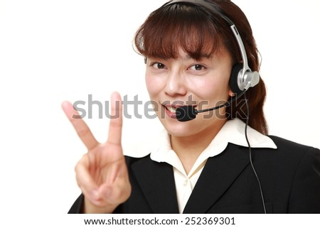 Businesswoman showing a victory sign - stock photo