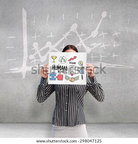 Businesswoman showing a white card in front of her face against grey room - stock photo