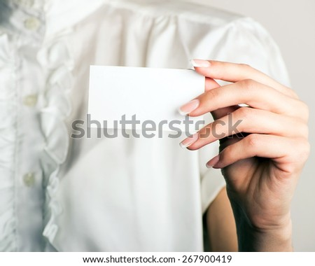 Businesswoman showing and handing a blank business card. Office background.