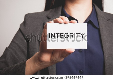 Businesswoman showing and handing an integrity card.