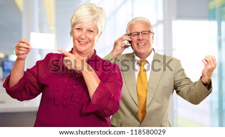 Businesswoman Showing Card In Front Of Man Using Cell Phone, Indoors - stock photo