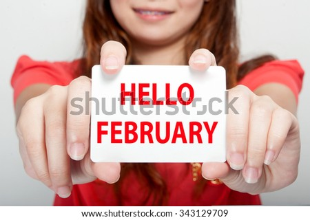 Businesswoman showing card with hello february message, - stock photo