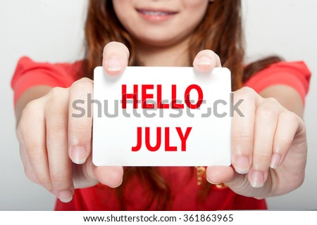 Businesswoman showing card with hello july message, - stock photo