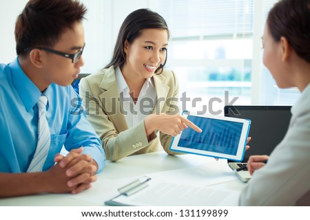 Businesswoman showing diagram to her colleagues - stock photo