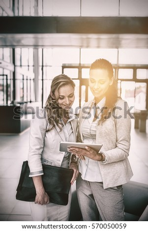 Businesswoman showing digital tablet to colleague in office