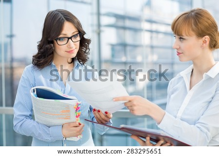 Businesswoman showing document to female colleague in office