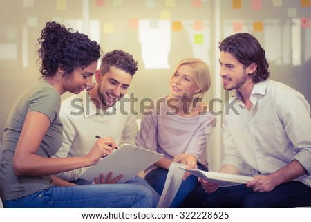 Businesswoman showing documents to colleagues in meeting at creative office - stock photo