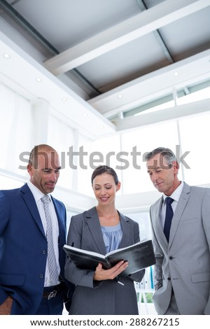 Businesswoman showing her notes to her colleagues in the office