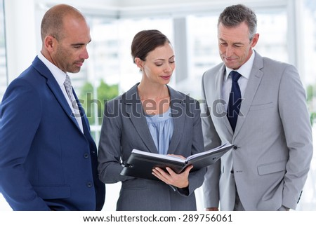 Businesswoman showing her notes to her colleagues in the office - stock photo