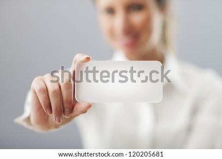 Businesswoman showing his business card. Shallow depth of field - focus on fingers and card. You can just add your text there. - stock photo