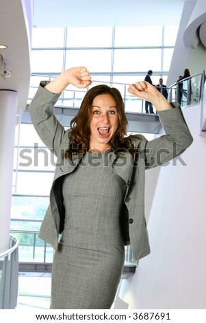 Businesswoman  showing joy and jubilation, both arms up in modern corporate interior with management team in background. - stock photo
