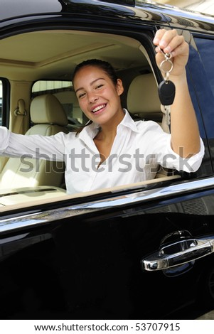 businesswoman showing keys of her new expensive  status vehicle - stock photo