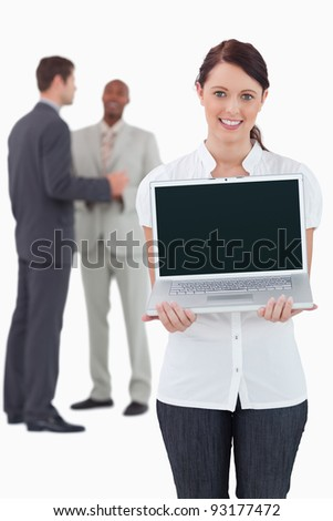 Businesswoman showing laptop with colleagues behind her against a white background - stock photo