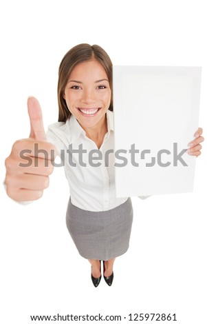 Businesswoman showing sign poster. Happy business woman giving thumb up holding an empty paperboard, with copyspace - stock photo
