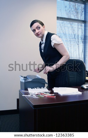 Businesswoman shredding documents at her desk - stock photo