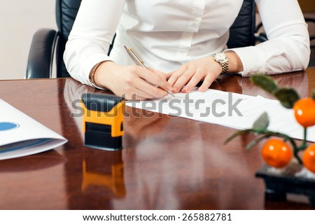 businesswoman signature document, working at her office - stock photo