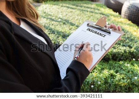 Businesswoman signing a insurance policy on the street. - stock photo